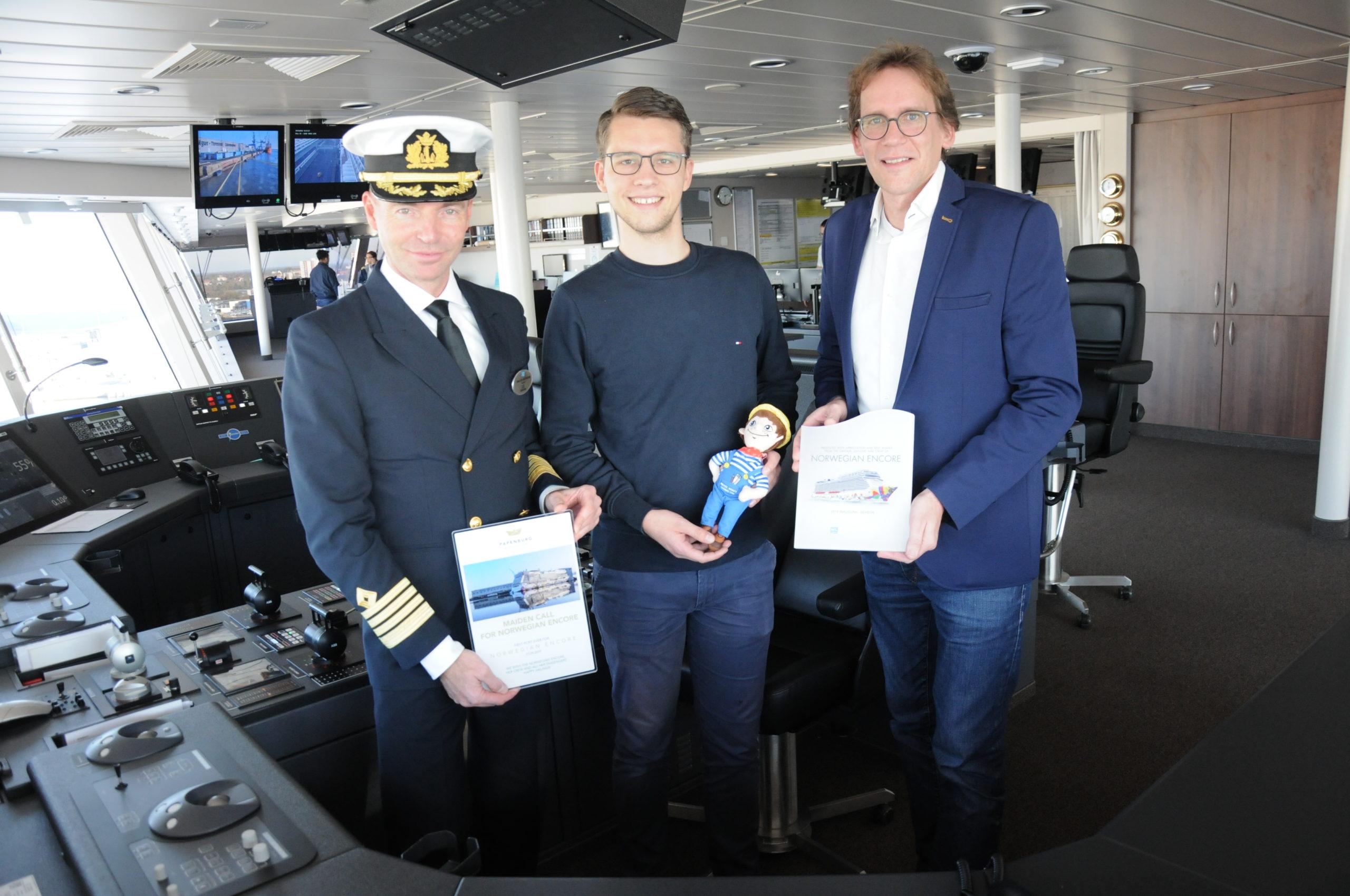 Plakettentausch auf der Brücke der Norwegian Encore: Kapitän Niklas Persson (links) freute sich über das Präsent von Werftsprecher Florian Feimann und PMG-Chef Kai Nehe (von links). Foto: Christoph Assies